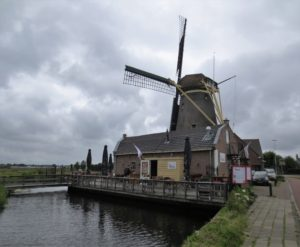 An image of a windmill with a small restaurant and canal.