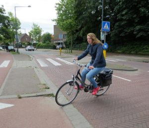 A woman cycling through a cycle crossing on a street.