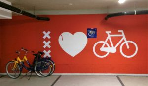 "A wall with two Netherlands bikeshare bikes leaving against a wall with an ""I heart bikes"" sign painted on."