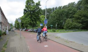 A bike path with two people on bikes beside a roadway that turns.