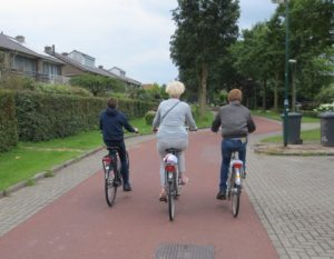 A female senior bikes between two teenage boys.