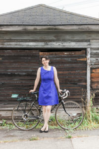 Picture of Cail with bike wearing blue dress in front of old garage